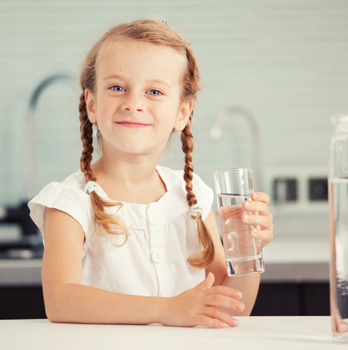 Niña con trenzas con un vaso de agua en la mano